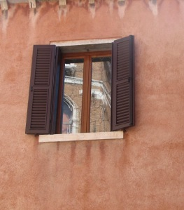 Window in stucco wall reflecting architexture